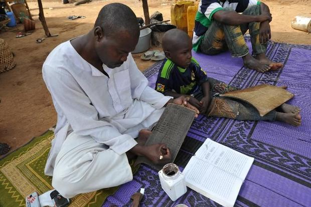 a-muslim-refugee-writes-on-a-wooden-tablet-in