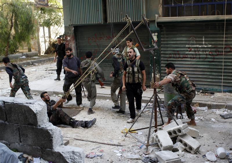 Members of the Free Syrian Army use a catapult to launch a homemade bomb during clashes with pro-government soldiers in the city of Aleppo
