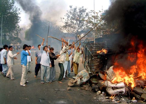 Mobs burn vehicles and scooters in the Asarva area of Ahmadabad, India, Thursday, Feb. 28, 2002. 58 people were killed in a train attack by a Muslim mob on Wednesday in the Indian state of Gujarat. The city of Ahmadabad was besieged by violence on Thursday to avenge the attack. (AP Photo/Siddharth Darshan Kumar)