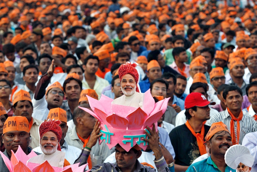 A supporter of Narendra Modi, the prime ministerial candidate for Bharatiya Janata Party, wears a headgear with a portrait of Modi during a rally in Ahmedabad