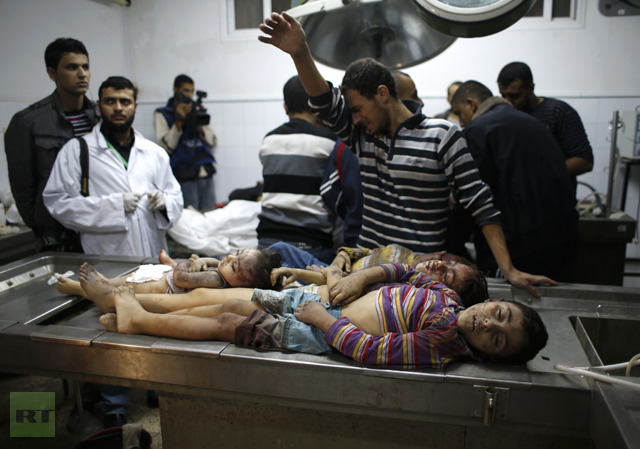 A Palestinian relative of four sibling children of the al-Dalo family, who were killed in an Israeli air strike, reacts as he stands next their bodies at a hospital in Gaza City