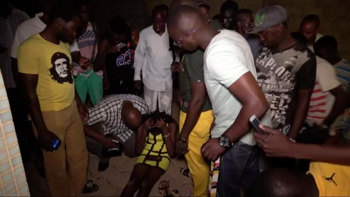 A wounded restaurant customer sits on the ground following an attack by gunmen on a restaurant in Ouagadougou