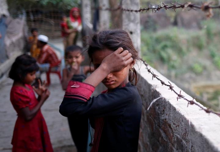A Rohingya refugee girl wipes her eyes as she cries at Leda Unregistered Refugee Camp in Teknaf